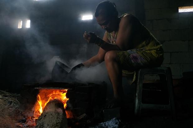 Yuk Tum, generasi kedua penerus kopi saring Mbok Tajeng saat menggoreng kopi.Foto/SINDONews/Tritus Julan